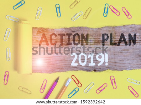 Handwriting text writing Action Plan 2019. Concept meaning proposed strategy or course of actions for current year Stationary and torn cardboard placed above a wooden classic table backdrop.
