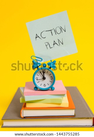 Handwriting text writing Action Plan. Concept meaning proposed strategy or course of actions for certain time Alarm clock note stacked notepads old books colored background. #1443755285