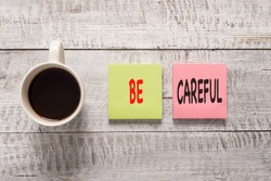 Handwriting text writing Be Careful. Concept meaning making sure of avoiding potential danger mishap or harm Stationary placed next to a cup of black coffee above the wooden table.
