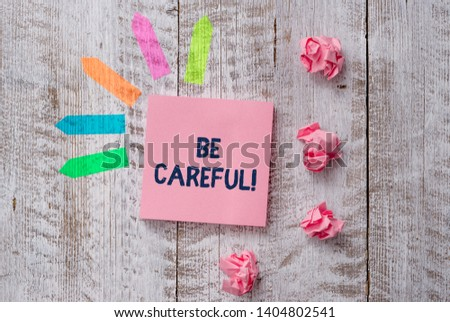 Handwriting text writing Be Careful. Concept meaning making sure of avoiding potential danger mishap or harm Plain note paper and line arrow stickers on the top of wooden table desk. #1404802541