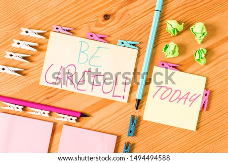 Handwriting text writing Be Careful. Concept meaning making sure of avoiding potential danger mishap or harm Colored clothespin papers empty reminder wooden floor background office. #1494494588