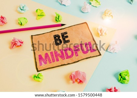 Handwriting text writing Be Mindful. Concept meaning paying close attention to or being conscious of something Colored crumpled papers empty reminder blue yellow background clothespin. #1579500448