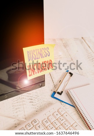 Handwriting text writing Business Incubator. Concept meaning company that helps new and startup companies to develop Note paper taped to black computer screen near keyboard and stationary.