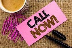 Handwriting text writing Call Now. Concept meaning Contact Talk Chat Hotline Support Telephony Customer Service written on Pink Sticky Note Paper on the jute background Coffee Cup Pen Pins.