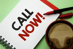 Handwriting text writing Call Now. Concept meaning Contact Talk Chat Hotline Support Telephony Customer Service written on Notebook Book on the plain background Coffee Cup next to it.