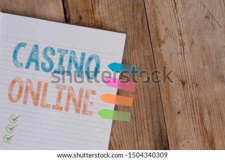 Handwriting text writing Casino Online. Concept meaning Computer Poker Game Gamble Royal Bet Lotto High Stakes Striped note book four colored arrow banners reminder wooden background. #1504340309