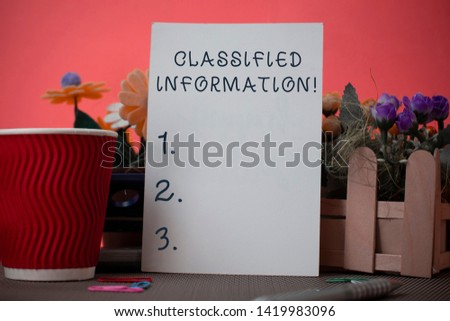 Handwriting text writing Classified Information. Concept meaning Sensitive Data Top Secret Unauthorized Disclosure Flowers and stationary plus plain sheet with paper big cup above a table.