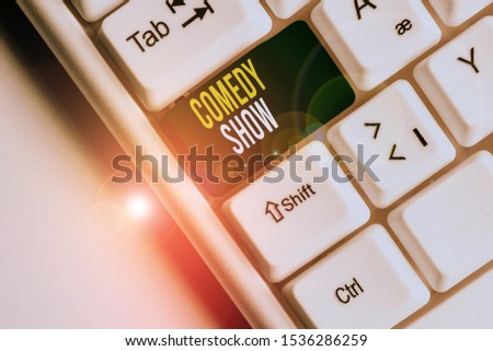 Handwriting text writing Comedy Show. Concept meaning Funny program Humorous Amusing medium of Entertainment White pc keyboard with empty note paper above white background key copy space. #1536286259