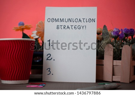 Handwriting text writing Communication Strategy. Concept meaning Verbal Nonverbal or Visual Plans of Goal and Method Flowers and stationary plus plain sheet with paper big cup above a table.