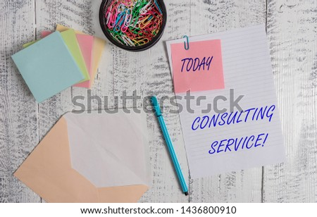 Handwriting text writing Consulting Service. Concept meaning Experts that offers knowledge to a third party for a fee Envelope sheet paper sticky note pads pen clips holder wooden background.