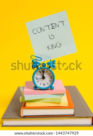Handwriting text writing Content Is King. Concept meaning believe that content is central to the success of a website Alarm clock note stacked notepads old books colored background.