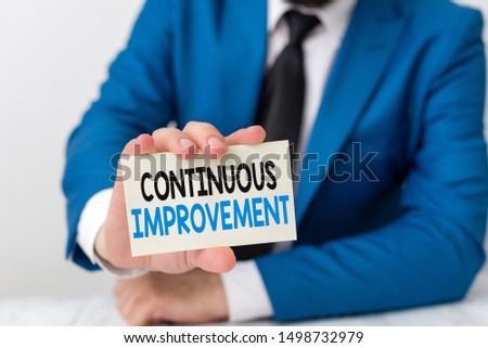 Handwriting text writing Continuous Improvement. Concept meaning ongoing effort to improve products or processes Man holds empty paper with copy space in front of him Space.