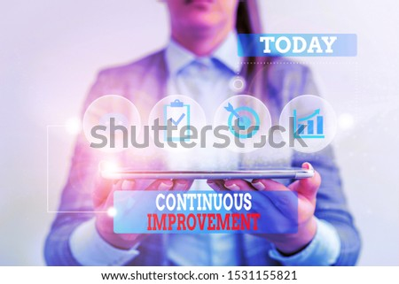 Handwriting text writing Continuous Improvement. Concept meaning ongoing effort to improve products or processes Female human wear formal work suit presenting presentation use smart device.