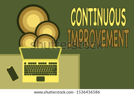 Handwriting text writing Continuous Improvement. Concept meaning ongoing effort to improve products or processes Upper view office working place laptop lying wooden desk smartphone side.