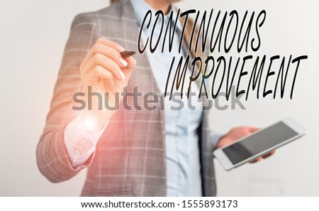 Handwriting text writing Continuous Improvement. Concept meaning ongoing effort to improve products or processes Business woman pointing in empty space with pen and mobile phone.
