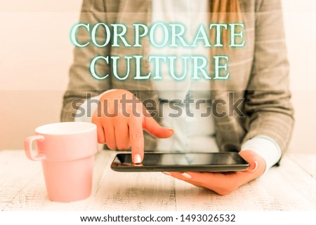 Handwriting text writing Corporate Culture. Concept meaning pervasive values and attitudes that characterize a company Business woman sitting with mobile phone and cup of coffee on the table. #1493026532