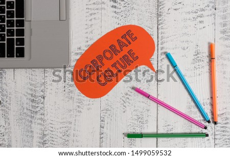 Handwriting text writing Corporate Culture. Concept meaning pervasive values and attitudes that characterize a company Open laptop blank speech bubble pens ballpoints lying vintage wooden table. #1499059532
