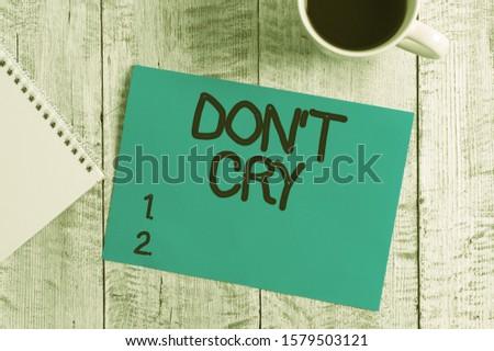 Handwriting text writing Don T Cry. Concept meaning Shed tears typically as an expression of distress pain or sorrow Stationary placed next to a cup of black coffee above the wooden table. #1579503121