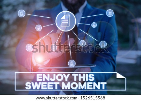 Handwriting text writing Enjoy This Sweet Moment. Concept meaning encouraging someone to love his life timeline Male human wear formal work suit presenting presentation using smart device.
