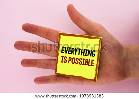 Handwriting text writing Everything Is Possible. Concept meaning All you think or dream can become true Optimistic written on Sticky Note Paper placed on the Hand on the plain background.