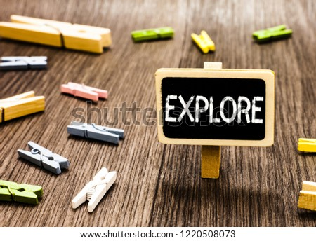 Handwriting text writing Explore. Concept meaning Travel somewhere unknown to learn about it Examine Evaluate Blackboard standing several clothespins disorganized messy wooden floor.