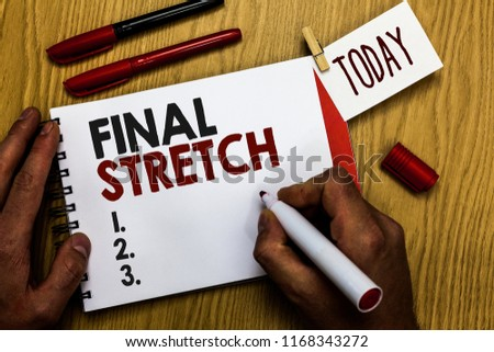 Handwriting text writing Final Stretch. Concept meaning Last Leg Concluding Round Ultimate Stage Finale Year ender Man holding marker notebook clothespin reminder wooden table cup coffee. #1168343272