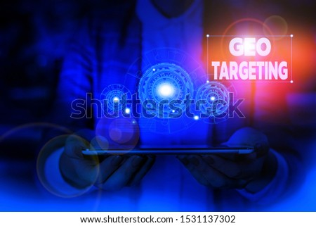 Handwriting text writing Geo Targeting. Concept meaning Digital Ads Views IP Address Adwords Campaigns Location Woman wear formal work suit presenting presentation using smart device.