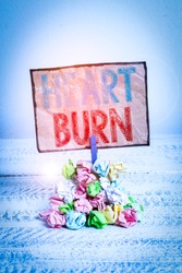 Handwriting text writing Heart Burn. Concept meaning a burning sensation or pain in the throat from acid reflux Reminder pile colored crumpled paper clothespin reminder white wooden space.