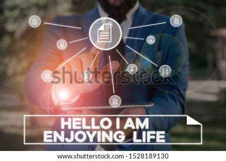 Handwriting text writing Hello I Am Enjoying Life. Concept meaning Happy relaxed lifestyle Enjoy simple things Male human wear formal work suit presenting presentation using smart device.