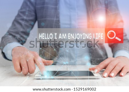 Handwriting text writing Hello I Am Enjoying Life. Concept meaning Happy relaxed lifestyle Enjoy simple things Female human wear formal work suit presenting presentation use smart device.