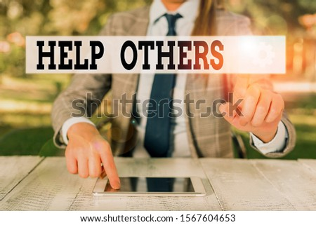 Handwriting text writing Help Others. Concept meaning the action of helping someone to do something or assistance Female business person sitting by table holding mobile phone.