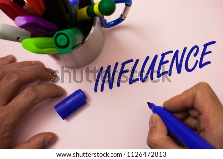 Handwriting text writing Influence. Concept meaning Capacity to have effect on others character development behavior Man working inspiration holding marker notebook ideas white background.