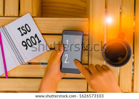 Handwriting text writing Iso 9001. Concept meaning designed help organizations to ensure meet the needs of customers woman computer smartphone drink mug office supplies technological devices.