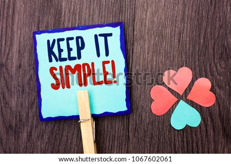 Handwriting text writing Keep It Simple Motivational Call. Concept meaning Simplify Things Easy Clear Concise Ideas written on Sticky Note Paper Holding With Clip on the wooden background Hearts.