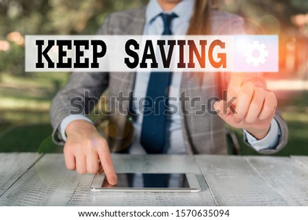 Handwriting text writing Keep Saving. Concept meaning keeping money in an account in a bank or financial organization Female business person sitting by table holding mobile phone.