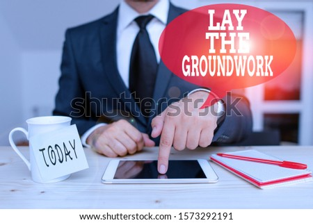 Handwriting text writing Lay The Groundwork. Concept meaning Preparing the Basics or Foundation for something Male human wear formal clothes present presentation use hi tech smartphone.