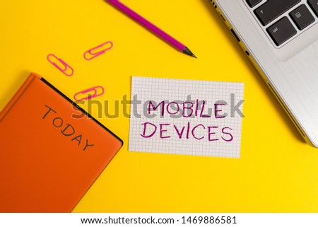 Handwriting text writing Mobile Devices. Concept meaning A portable computing device like smartphone tablet computer Laptop clips pencil paper sheet hard cover notebook colored background. #1469886581