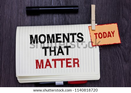 Handwriting text writing Moments That Matter. Concept meaning Meaningful positive happy memorable important times Written paper on wooden desk paper clip grip note with red words black pen. #1140818720