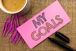Handwriting text writing My Goals. Concept meaning Goal Aim Strategy Determination Career Plan Objective Target Vision written on Pink Sticky Note Paper on the jute background Coffee Cup Pen Pins.
