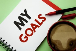 Handwriting text writing My Goals. Concept meaning Goal Aim Strategy Determination Career Plan Objective Target Vision written on Notebook Book on the plain background Coffee Cup next to it.
