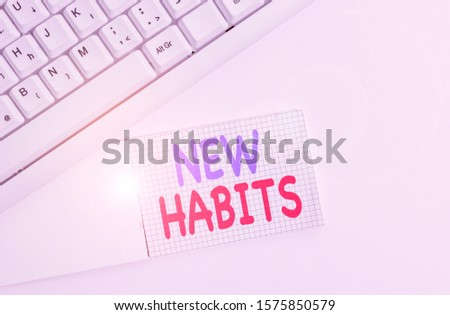 Handwriting text writing New Habits. Concept meaning change the routine of behavior that is repeated regularly White pc keyboard with empty note paper above white background.