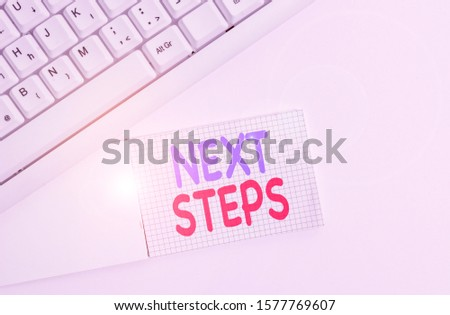 Handwriting text writing Next Steps. Concept meaning numper of process going to be made after current one planning White pc keyboard with empty note paper above white background. #1577769607