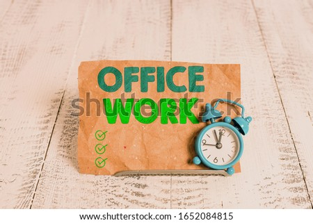 Handwriting text writing Office Work. Concept meaning any clerical or administrative work for an organization Mini blue alarm clock stand tilted above buffer wire in front of notepaper. Stock fotó ©