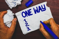 Handwriting text writing One Way. Concept meaning Only direction Street sign Traffic regulation route indication Man holding marker notebook page crumpled papers several tries mistakes.