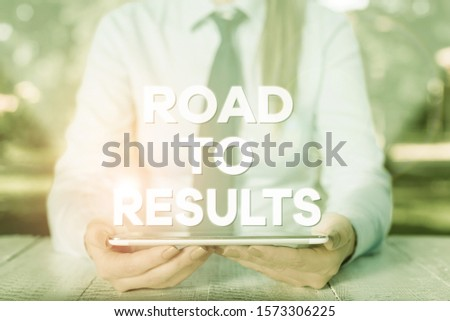 Handwriting text writing Road To Results. Concept meaning Business direction Path Result Achievements Goals Progress Female business person sitting by table and holding mobile phone.