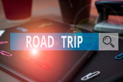 Handwriting text writing Road Trip. Concept meaning Roaming around places with no definite or exact target location Scissors and writing equipments plus math book above textured backdrop.