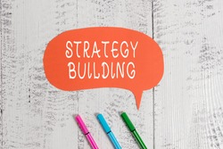 Handwriting text writing Strategy Building. Concept meaning Leveraging Buying and acquiring others platforms Ballpoints blank colored speech bubble wooden rustic vintage background.