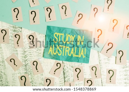 Handwriting text writing Study In Australia. Concept meaning going into foreign country order complete your studies Scribbled and crumbling papers with thick cardboard above wooden table.