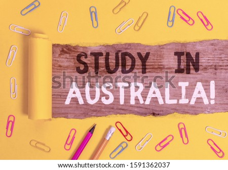 Handwriting text writing Study In Australia. Concept meaning going into foreign country order complete your studies Stationary and torn cardboard placed above a wooden classic table backdrop.