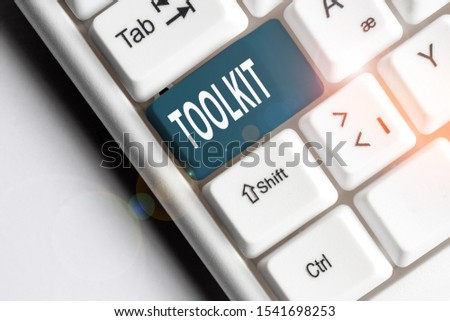 Handwriting text writing Toolkit. Concept meaning set of tools kept in a bag or box and used for a particular purpose White pc keyboard with empty note paper above white background key copy space. #1541698253